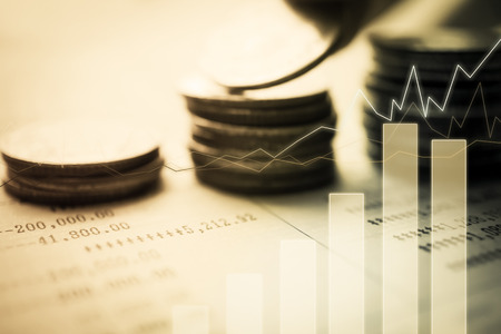 Double exposure of graph and rows of coins for finance and banking concept