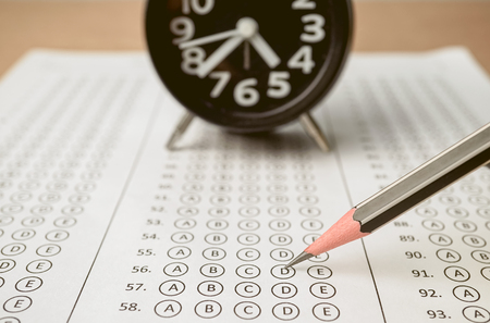 answer sheet , alarm clock and pencil for education concept