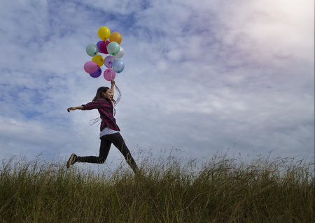 Beautiful girl holding balloons running in prairie grass. On a clear day Stock Photo