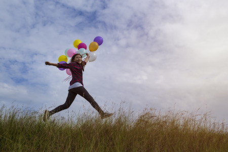 Beautiful girl holding balloons Jumping in prairie grass. On a clear day Stock Photo