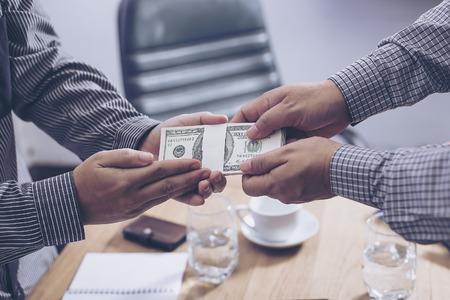 venal: Giving a bribe into a pocket to negotiate business. Closeup shot Stock Photo