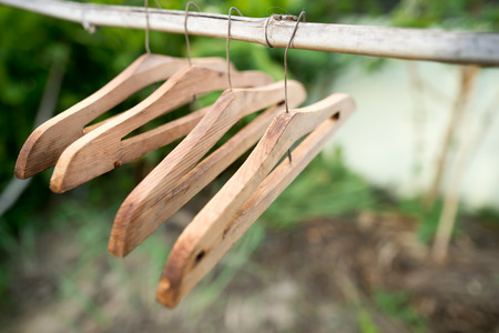 hung: Old wooden hangers hung on a clothes line.
