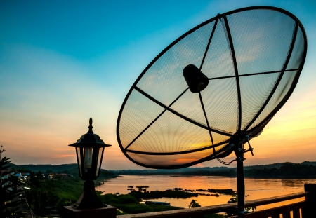 dish disk: Satellite dish near the river at sunset Stock Photo