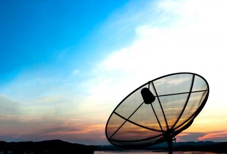 Satellite dish near the river at sunset Standard-Bild