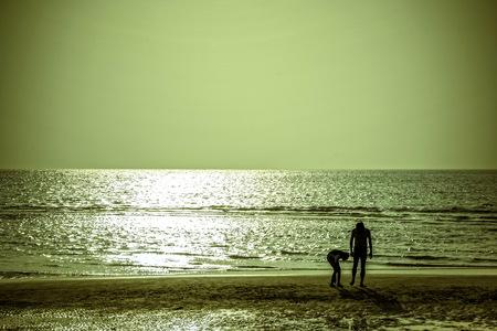 Tourists walk on the beach at sunset Standard-Bild
