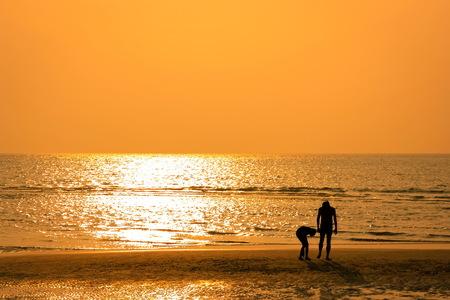 Touristen zu Fuß am Strand bei Sonnenuntergang Standard-Bild - 50899613