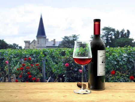 バック グラウンドでシャトーと架空のボルドーの赤ワインのグラスとボトル