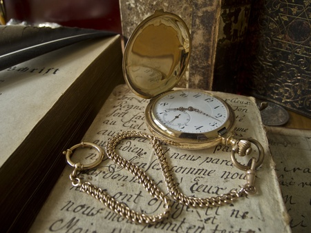 heirloom: ancient golden pocket watch lying on an antique handwritten sheet of paper