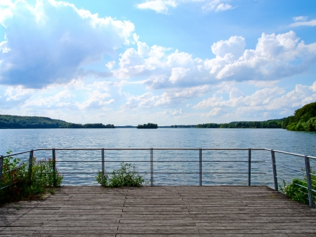 a wooden terrace with a beautiful view to the lake Foto de archivo