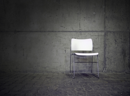 white chair in spotlight with concrete wall in the background photo