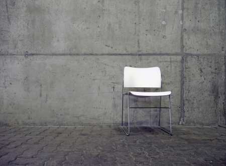 avant: white chair in front of face concrete wall Stock Photo