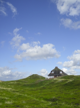 lonesome house with thatched roof in the dunes photo