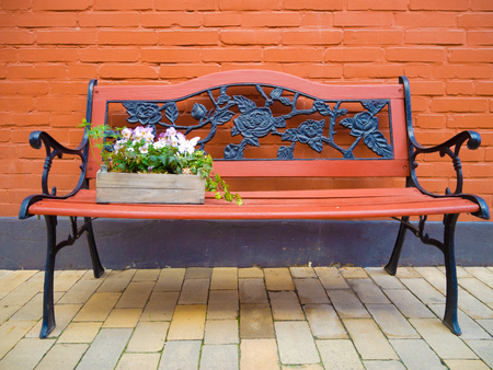 vintage bench of wood and cast iron with flowers photo