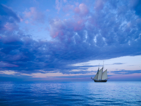 seafaring: ancient two-mast schooner sailing away to the horizon