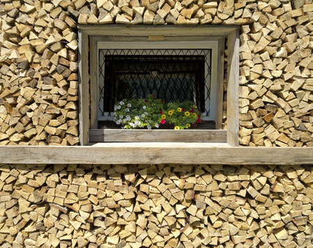 a stack of fire wood surrounding a rural window