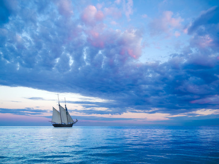 windless: ancient two-mast schooner sailing away to the horizon