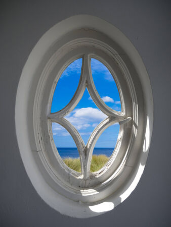 ancient oval window with a view to the sea photo