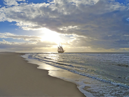 schooner: a sailing ship close to the beach in moody sunset