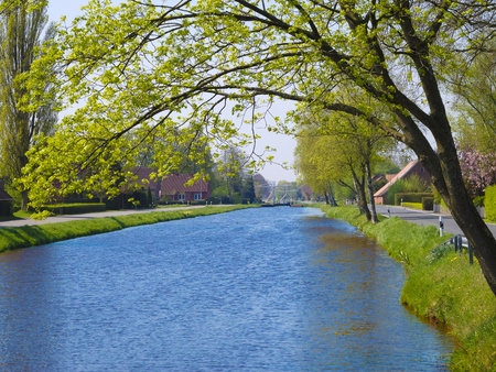 pointed: landscape in spring with beautiful village by a canal