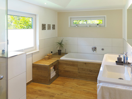 modern bathroom with wooden floor, bathtub, sink and windows Stock Photo