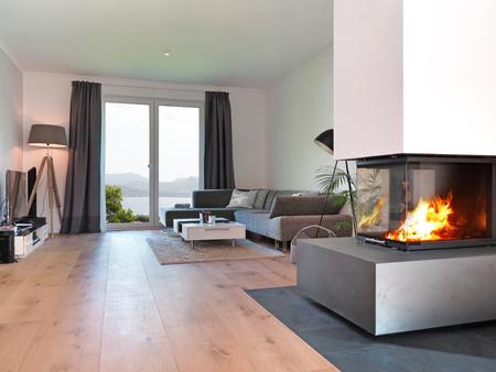 suelos: moderna sala de estar con chimenea y vistas a la costa Foto de archivo