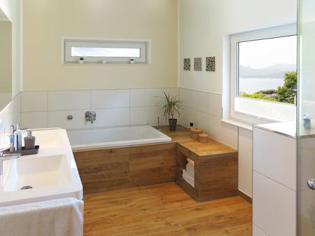 downlight: modern bathroom with wooden floor, windows and a view to the sea