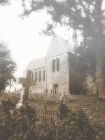 old church: overgrown crosses in ancient graveyard and church in the mist