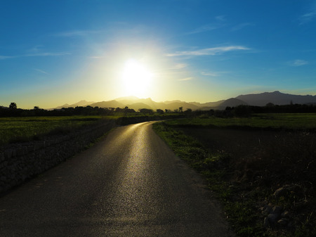 lonesome: lonesome countryroad leading to the mountains in contre-jour Stock Photo