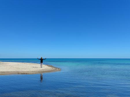 sandbank: woman on sandbank spreading her arms and welcoming the sea Stock Photo