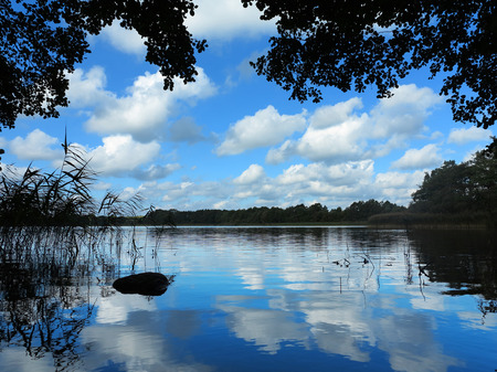 lonesome: lonesome idyllic lake in beautiful natural landscape reflecting cloudy blue sky Stock Photo