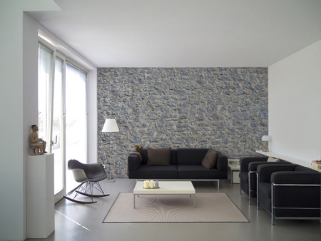 living room with natural stone wall and copyspace for your own images Stock Photo