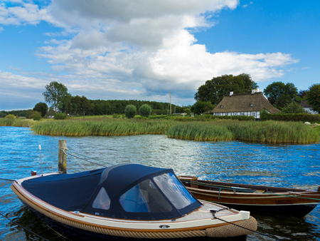 idyllic scenery with boats in the water and beautiful cottage in the background