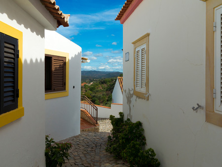 Lane in a village between houses with a view to the mountain landscape in Stock fotó