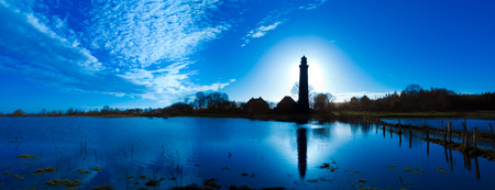 panoramic landscpae with Lighthouse in Behrensdorf in contre jour twilight Stock fotó