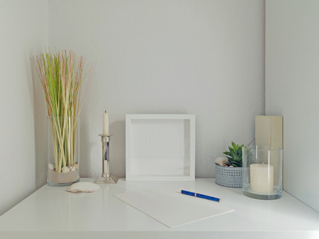modern white desk interior design with decoration elements, frame for pictures and white wall in the background Stock fotó