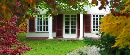 White retro style vintage mansion with windows and french doors surounded by garden in autumn 版權商用圖片