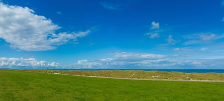panoramic landscape with cycle path between dunes and dyke with a view to the sea