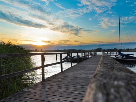 idyllic landscape with beautiful sunset, a wooden jetty and some boats in the lake Stock fotó