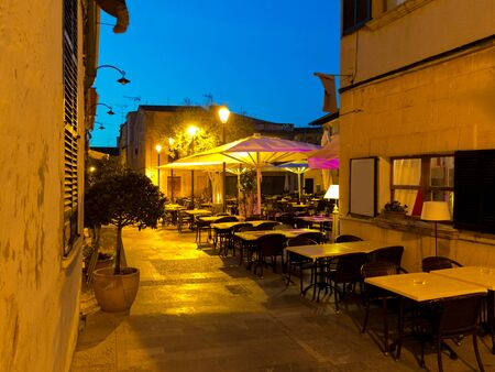 restaurants on the public market place in the lanes of the old town of Alcudia Majorca by night Stock fotó - 137561646