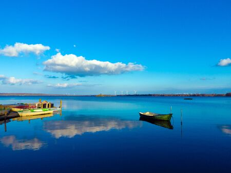 beautiful, calm and idyllic landscape with fishing boats in a lake short before sunset Stock fotó