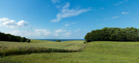 panoramic rural countryside landscape with field and pasture and the coast of the baltic sea in the background
