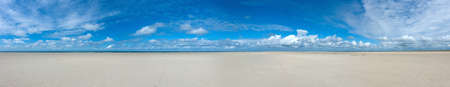 endless empty panoramic northsea beach background with wide sands an blue cloudy sky in the north of the island Fanø in Denmark