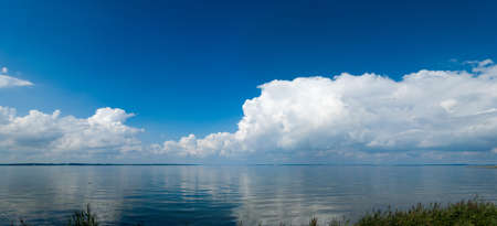 panoramic landscape at the Flensburg fjord with calm sea and impressive clouds reflecting in the water