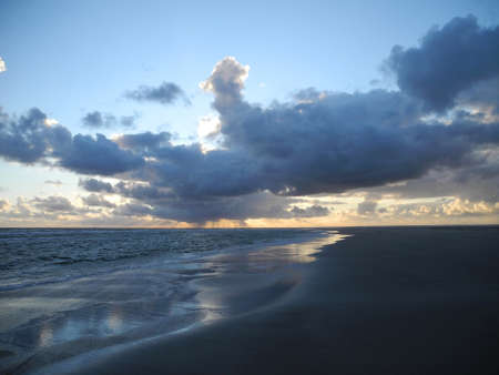 empty north sea beach landscape during sunset with impressing sky and clouds