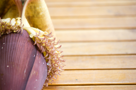 Banana blossoms on brown wood floor.
