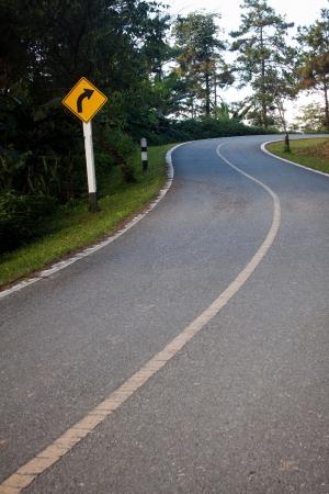 Dangerous curve sign on the hillside road photo
