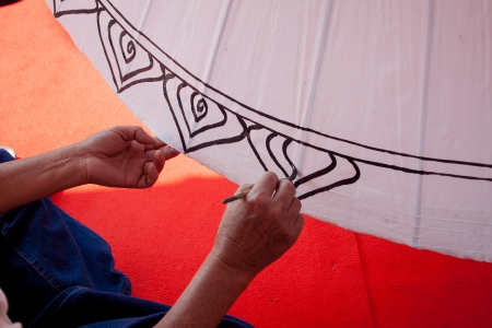 Coloring paints umbrella made of paper   fabric  Arts and crafts of the village Bo Sang, Chiang Mai Thailand  photo