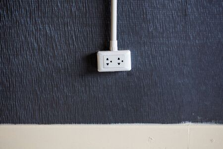 balck: Single Electric plug on balck Wall Stock Photo
