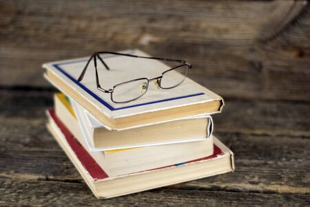 university choice: Stack of old books and glasses on a wooden background, shallow dof