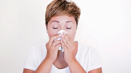 catarrh: Short haired woman blowing her nose on the white background. Seasonal diseases. Allergies. Cold in the head. Sneeze. Stock Photo